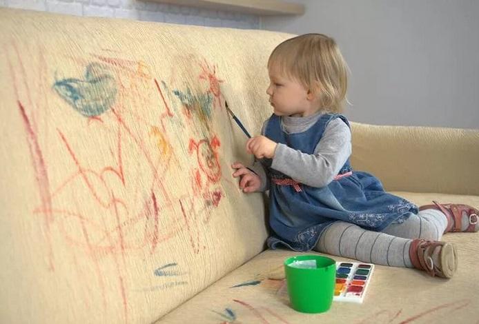 ребенок рисует на диване